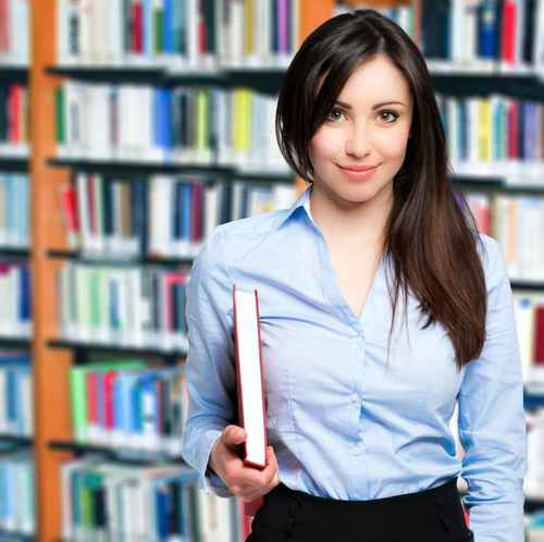 Smiling teacher holding a book in a library